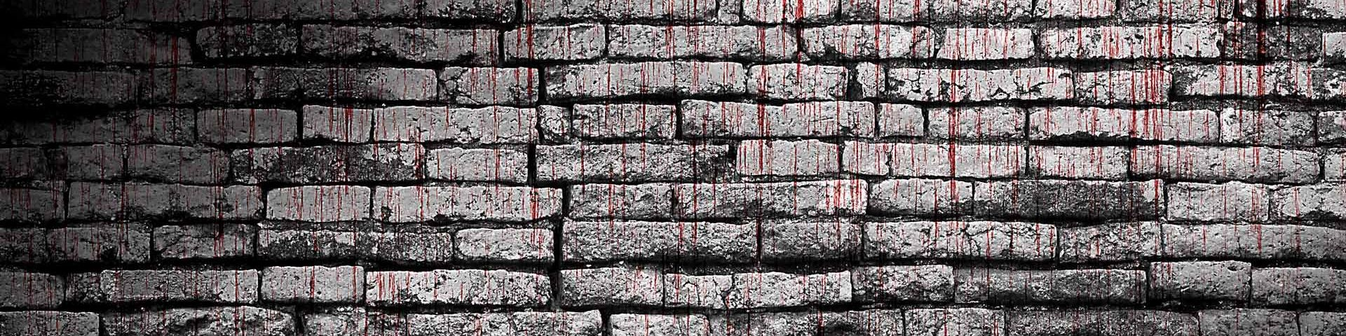 An old grey brick wall, with red blood dripping down it.